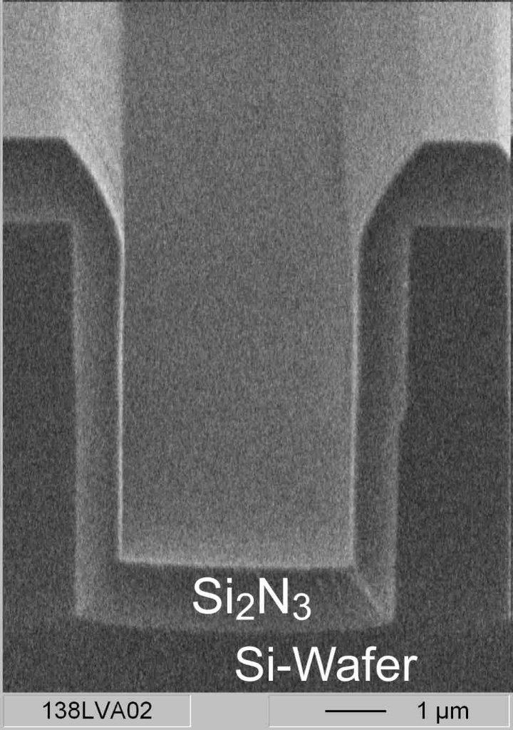The breaking edge of a silicon wafer shows the silicon nitride barrier layer in a microstructure. (c)