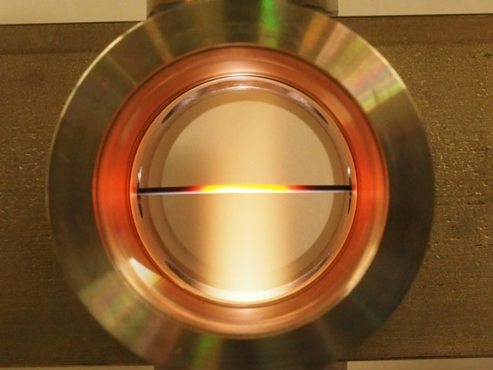 Tubular reactor with a ceramic capillary  inside during operation with an air plasma. (c)